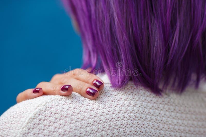 Purpura robiąca manikiur dotyka z dziewczyną z purpurowym włosy fotografia stock