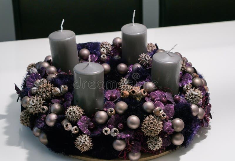 Purpurfärgad adventkrans med struntsaker och fyra gråa stearinljus på en vit tabell royaltyfri fotografi