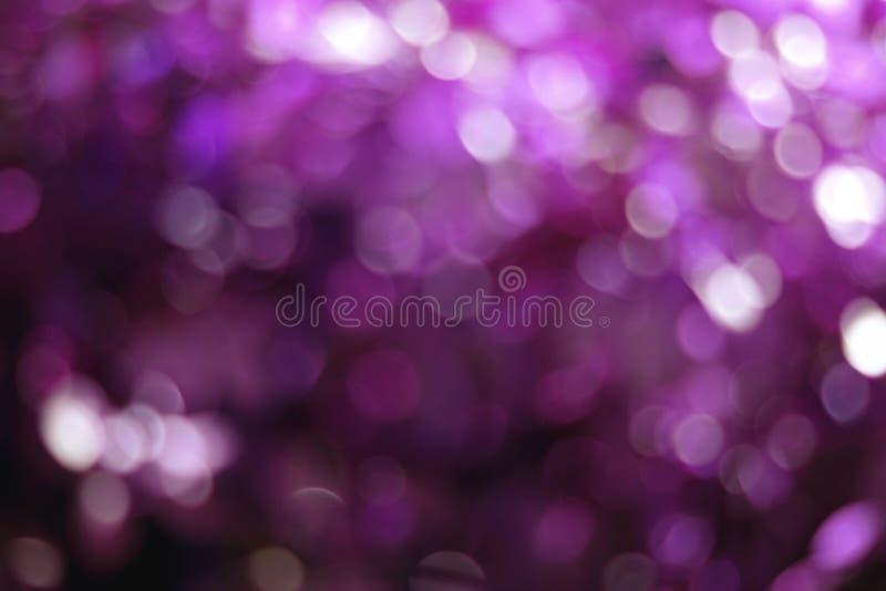 Purpurfärgad bokeh tänder bakgrund som är färgrik blänker defocused fotografering för bildbyråer