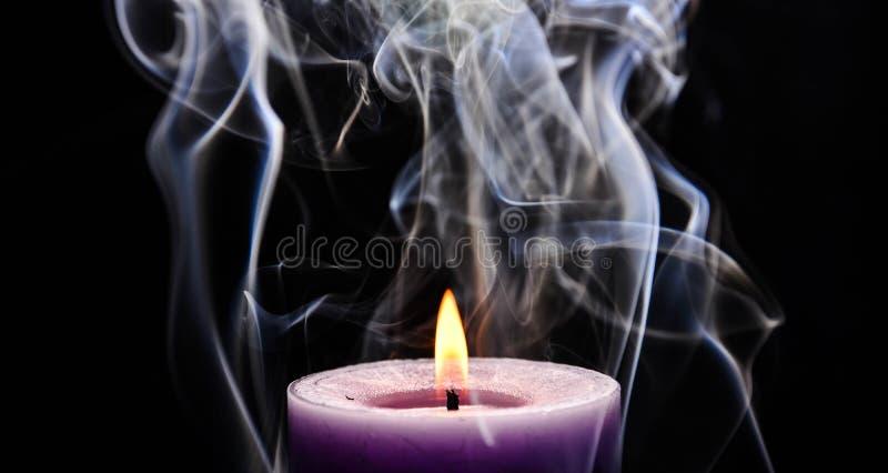 Purpurfärgad bränningstearinljus arkivfoton