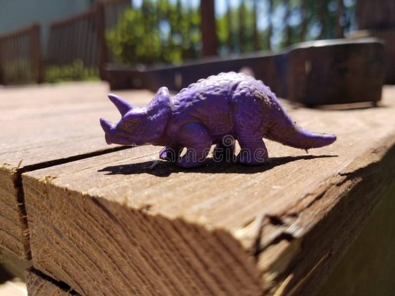 Purpurfärgad dinosaurie på däck royaltyfri fotografi