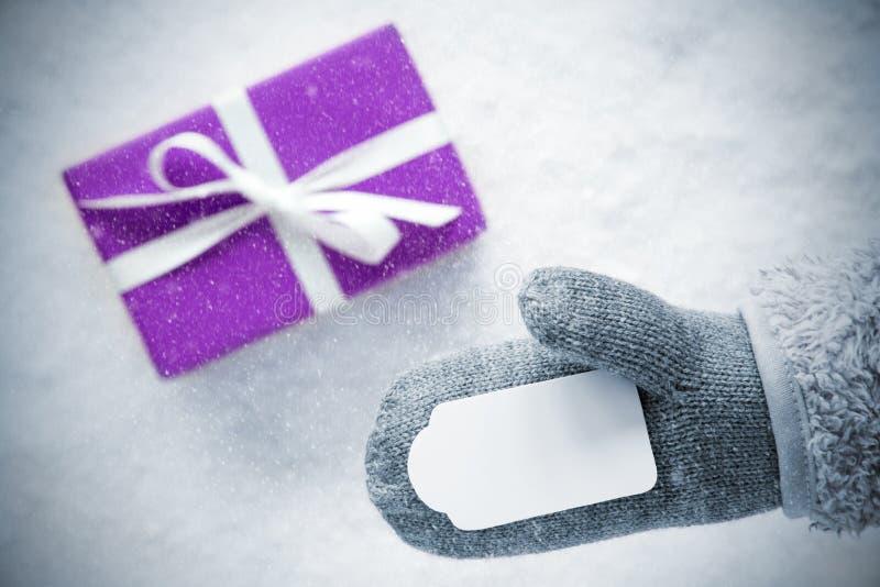 Purpurfärgad gåva, handske, kopieringsutrymme, snöflingor royaltyfri fotografi