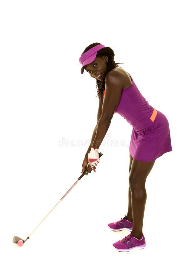 Purpurfärgad golf för afrikansk amerikankvinna som är klar att svänga leende royaltyfri fotografi