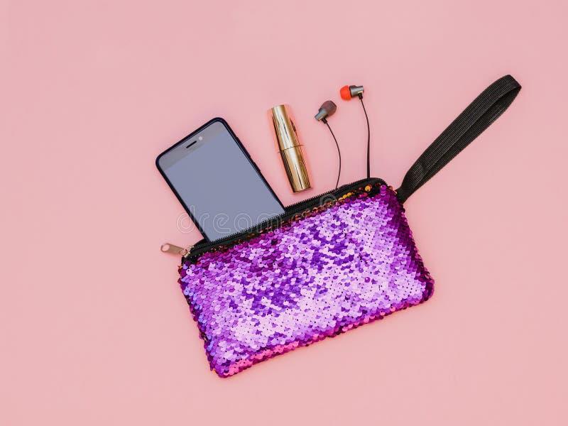 Purpurfärgad handväska för kvinna` s med telefonläppstift och hörlurar på en rosa tabell Pastellfärgad färg Lekmanna- lägenhet royaltyfria foton