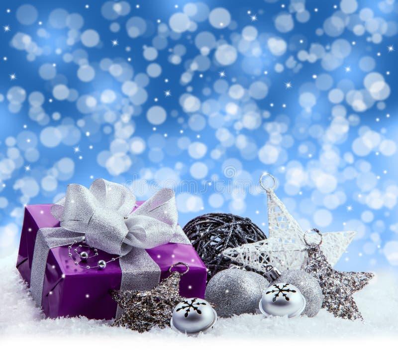 Purpurfärgad jul packe, gåva av ett silverband Klirrklockor, silverjulbollar och pålagd snö för julstjärnor Abstrac arkivbild