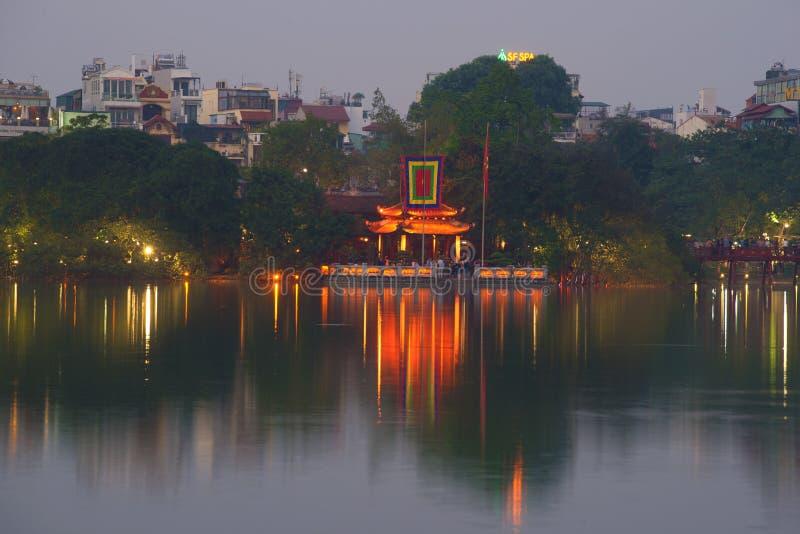 Purpurfärgad skymning på Hoan Kiem sjön Sikt av templet av Jade Mountain arkivbilder