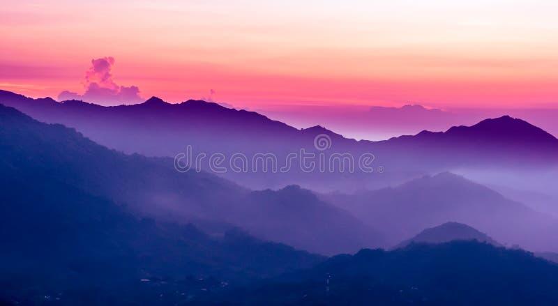 Purpurfärgad solnedgång i bergen arkivbilder