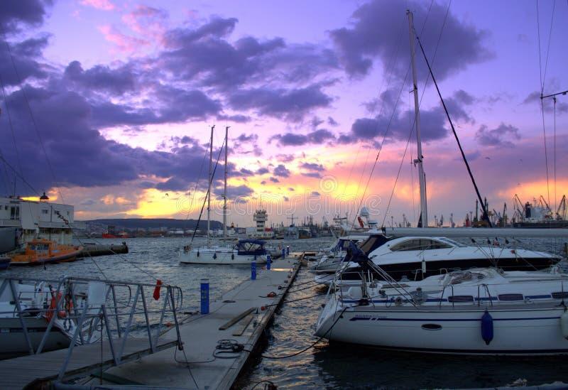 Purpurfärgad solnedgånghimmel över yachtport arkivfoton