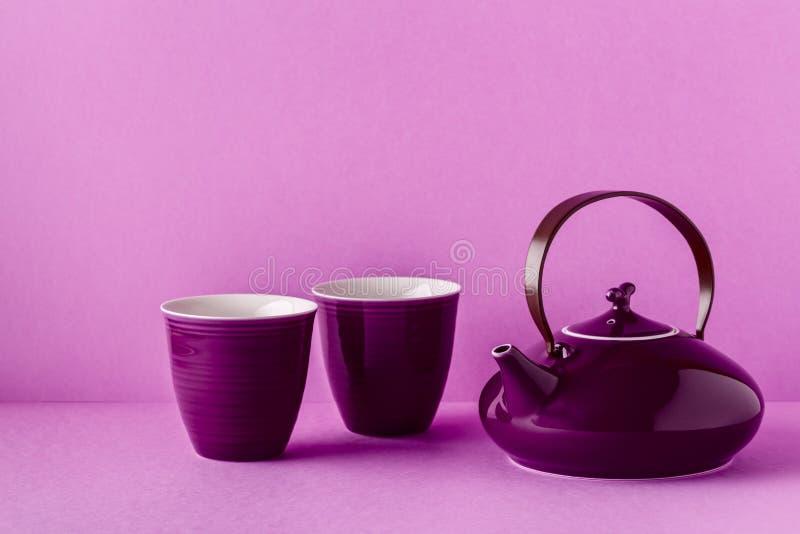Purpurfärgad tekanna och koppar på en lila bakgrund arkivbild