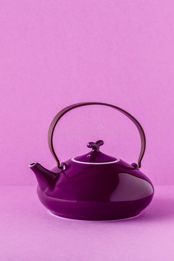 Purpurfärgad tekanna och koppar på en lila bakgrund arkivfoto