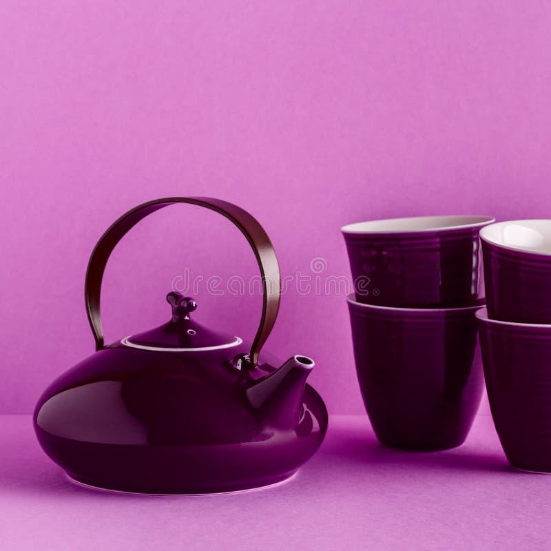 Purpurfärgad tekanna och koppar på en lila bakgrund arkivbilder