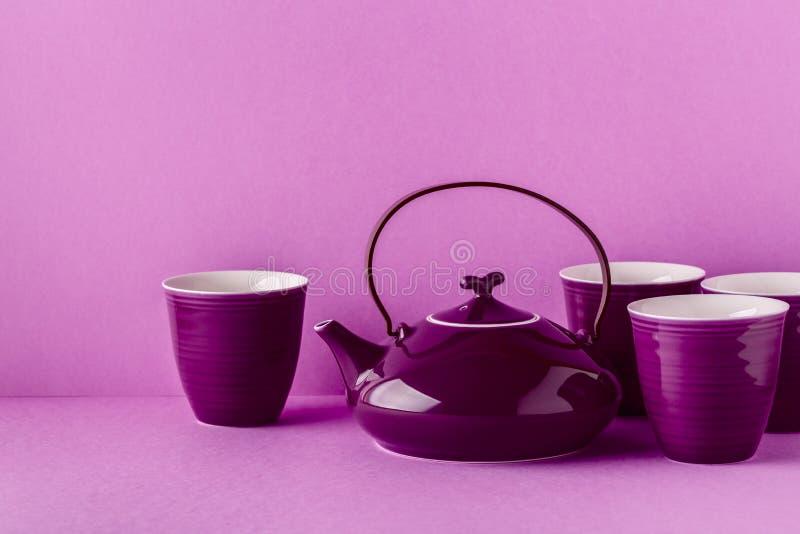 Purpurfärgad tekanna och koppar på en lila bakgrund royaltyfri fotografi