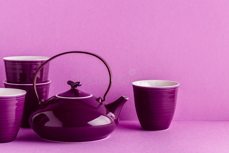 Purpurfärgad tekanna och koppar på en lila bakgrund arkivfoton