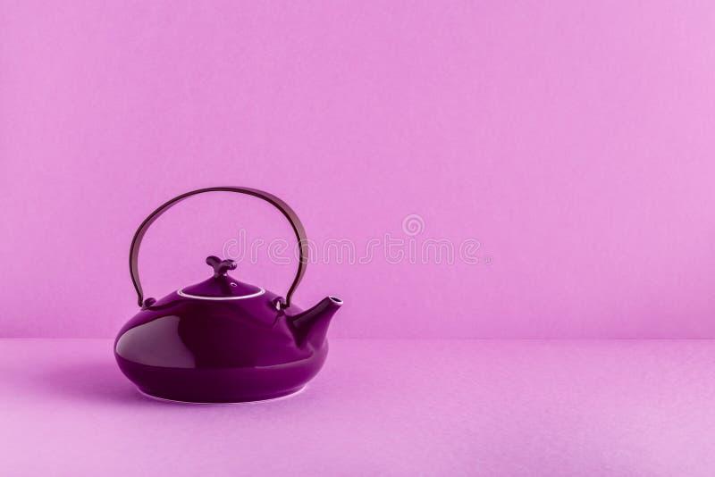 Purpurfärgad tekanna och koppar på en lila bakgrund royaltyfri bild