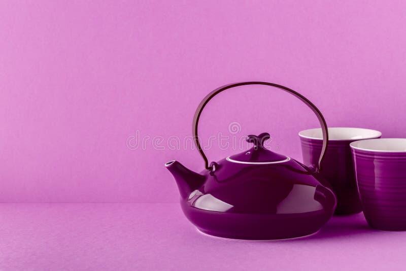 Purpurfärgad tekanna och koppar på en lila bakgrund royaltyfria foton
