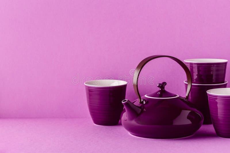 Purpurfärgad tekanna och koppar på en lila bakgrund fotografering för bildbyråer