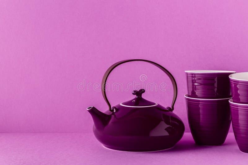 Purpurfärgad tekanna och koppar på en lila bakgrund royaltyfria bilder