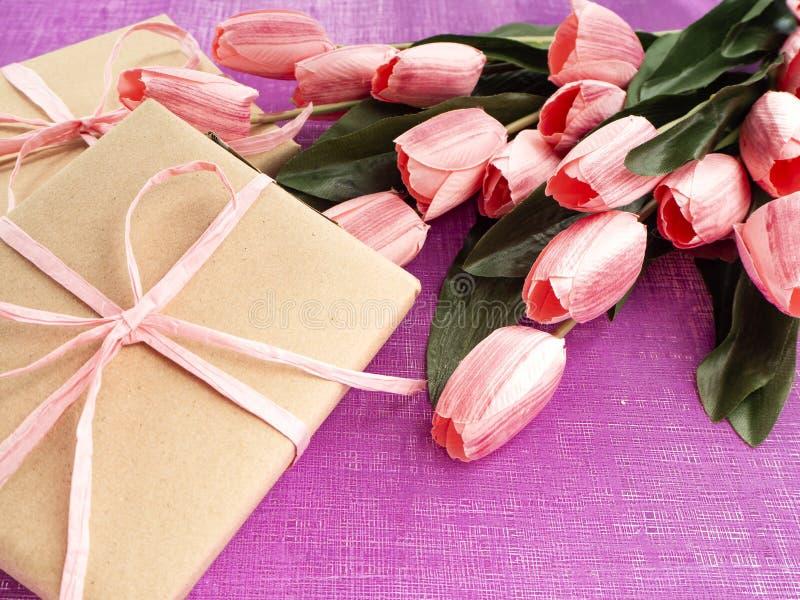 Purpurfärgad tulpan- och gåvaask på purpurfärgad bakgrund royaltyfri fotografi