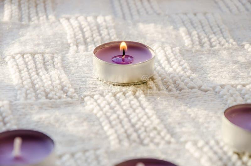 Purpurfärgade aromatiska stearinljus på en halsduk arkivbilder