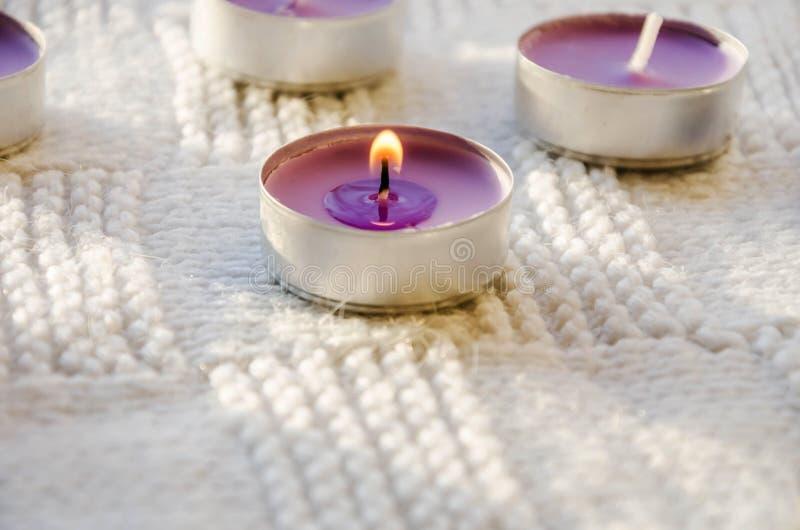 Purpurfärgade aromatiska stearinljus på en vit bakgrund arkivfoto