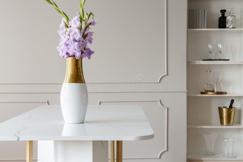 Purpurfärgade blommor för lavendel i en vas på en vit marmortabell i en elegant matsalinre med stöpningen på beigea väggar royaltyfria bilder