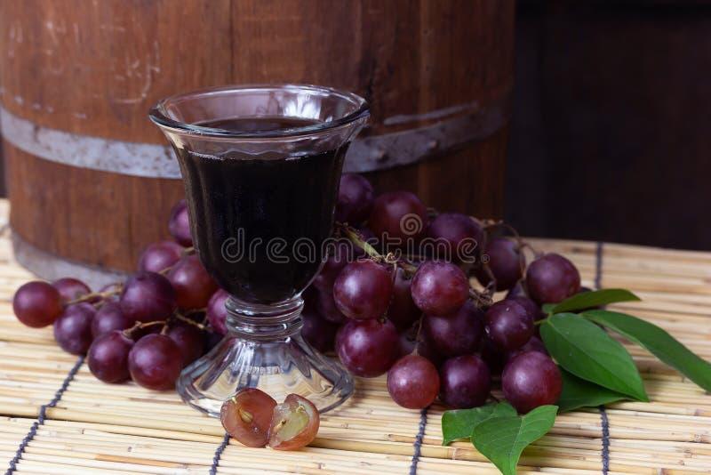 Purpurfärgade druvor med druvafruktsaft royaltyfria foton