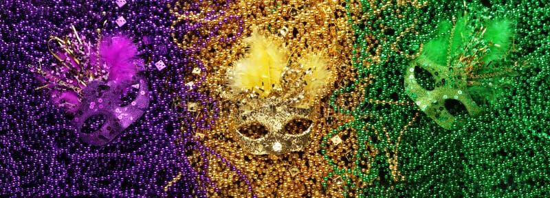Purpurfärgade, guld- och gröna Mardi Gras pärlor och maskeringar arkivfoton