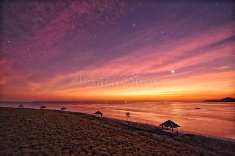 Purpurfärgade himlar för solnedgång på den breda månen för strandhavhonung arkivfoto