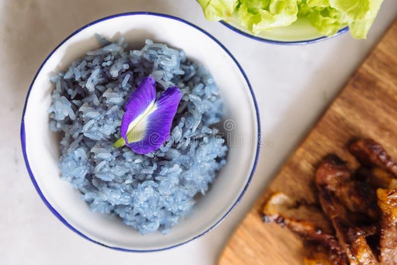 Purpurfärgade klibbiga ris för fjärilsärta som dekoreras med blomman för fjärilsärta Thailändsk mat för fusion royaltyfri fotografi