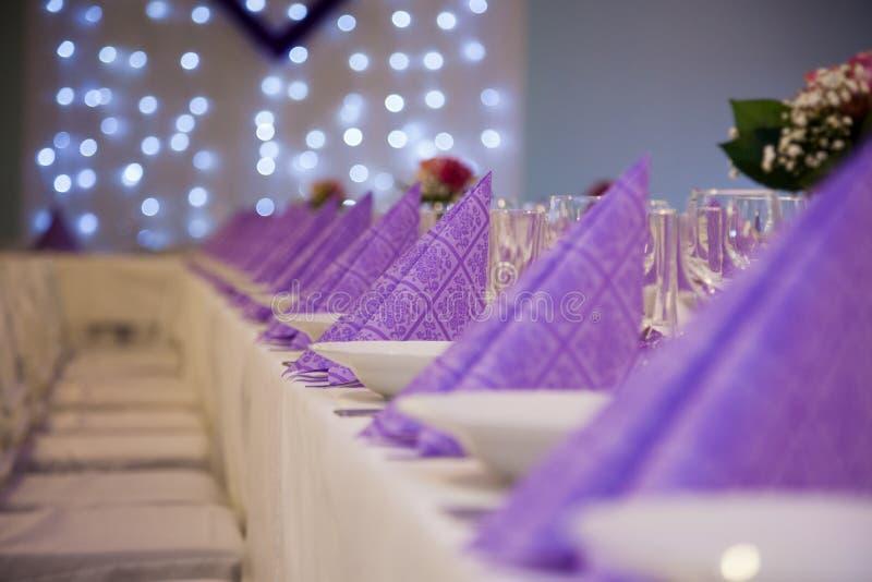 Purpurfärgade servetter på brölloptabellen royaltyfri fotografi