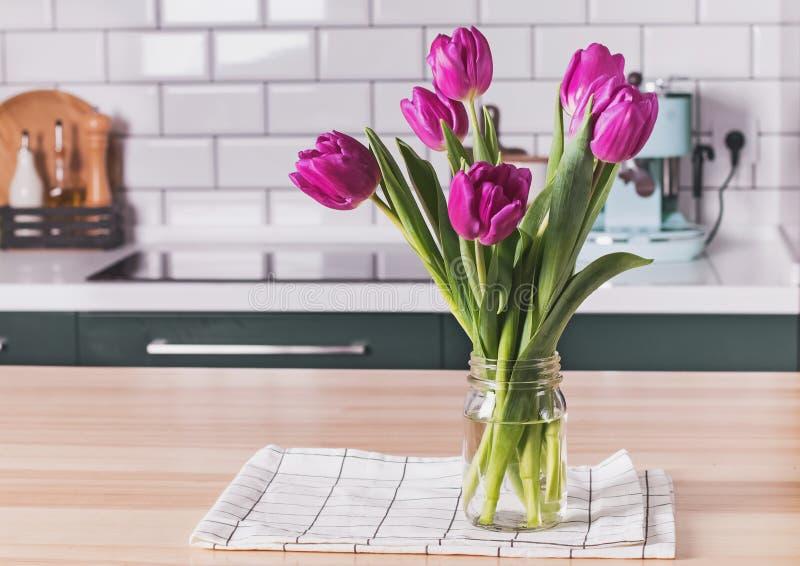 Purpurfärgade tulpan i ett exponeringsglaskrusanseende på det moderna köket royaltyfri foto