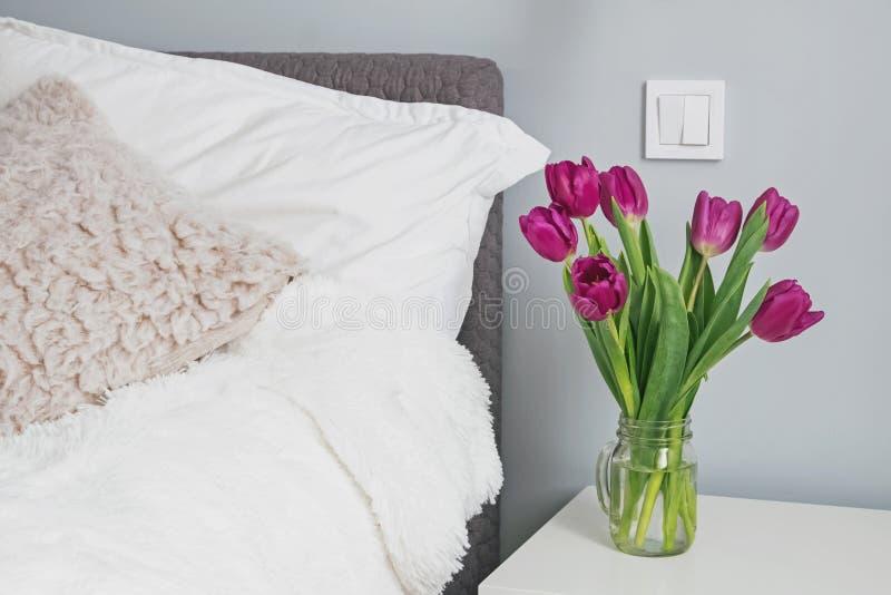 Purpurfärgade tulpan som står på en nightstand i det moderna vita sovrummet nära sängen royaltyfria foton