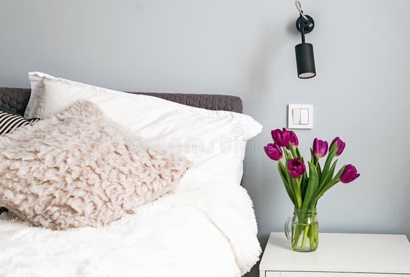 Purpurfärgade tulpan som står på en nightstand i det moderna vita sovrummet nära sängen royaltyfri foto