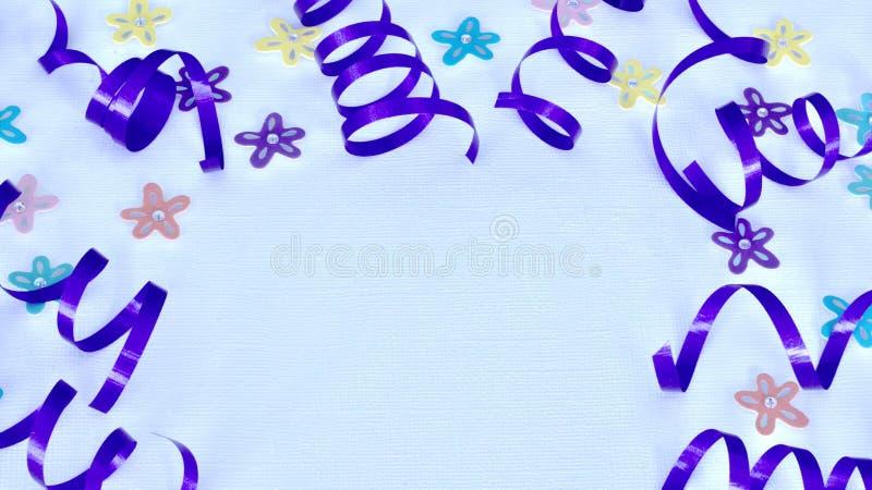 Purpurfärgat band och blommor på vit bakgrund royaltyfria bilder