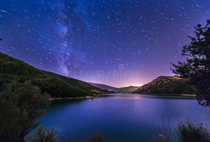 Purpurfärgat landskap för sjö för stjärnor för natthimmel med den mjölkaktiga vägen på berget royaltyfri foto