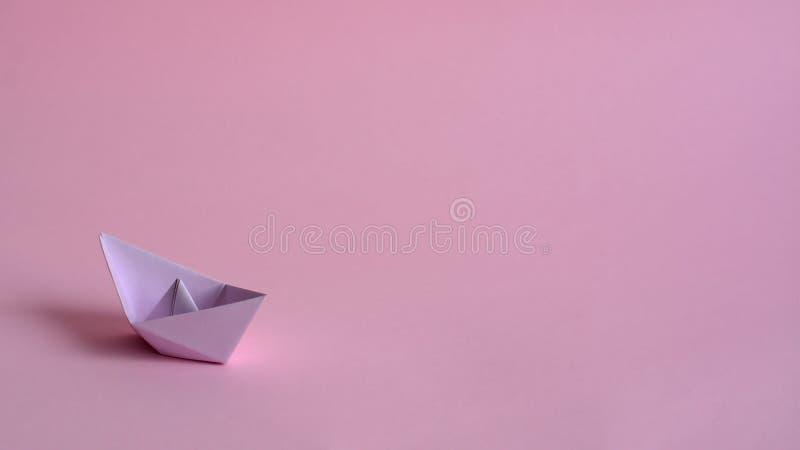 Purpurfärgat pappers- fartyg på ett ljust - rosa bakgrund fotografering för bildbyråer