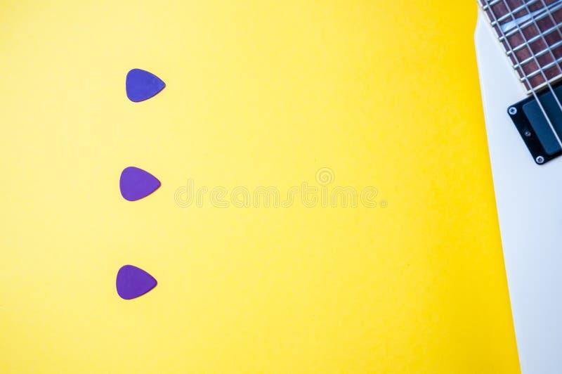 Purpurf?rgade hackor f?r gitarr som streck, med kopieringsutrymme p? gul ljus bakgrund Del av den vita elektriska gitarren på rät arkivfoto