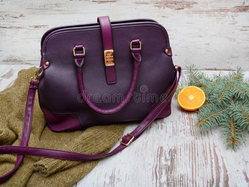 Purpurowa damy torba, ciepły pulower na drewnianym tle, świerczyny gałąź i pomarańcze, piękna błękitny jaskrawy pojęcia twarzy mo obraz royalty free