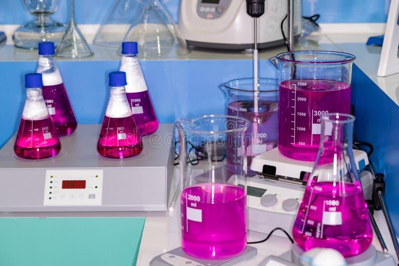 Purpurowe ciekłe kolby w laboratorium badawczym zdjęcia stock