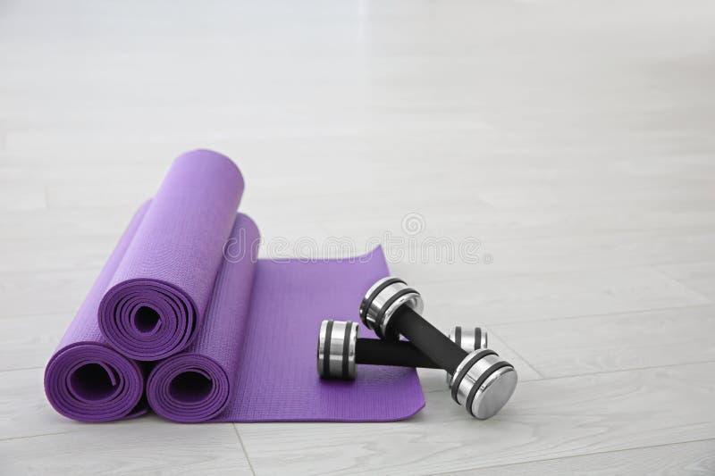 Purpurowe joga maty, dumbbells i fotografia stock