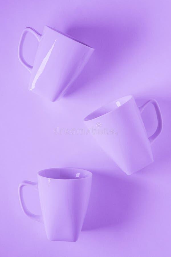 3 purpurowego kawowego kubka na purplish tle rozpraszającym z pustą kopii przestrzenią zdjęcia stock