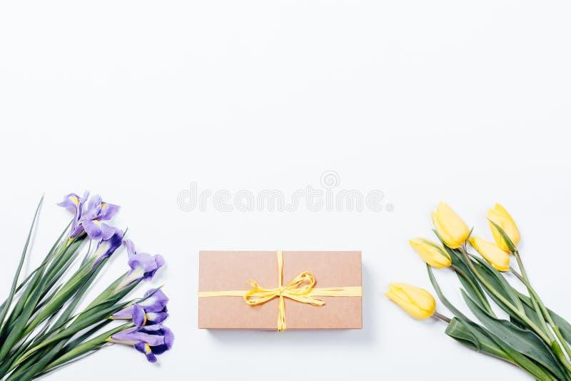 Purpurowi irysy, żółci tulipany i prezenta pudełko z łękiem na bielu plecy, zdjęcie royalty free