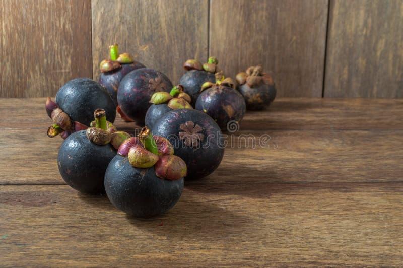 Purpurowi mangostany na drewnianym tle obraz stock