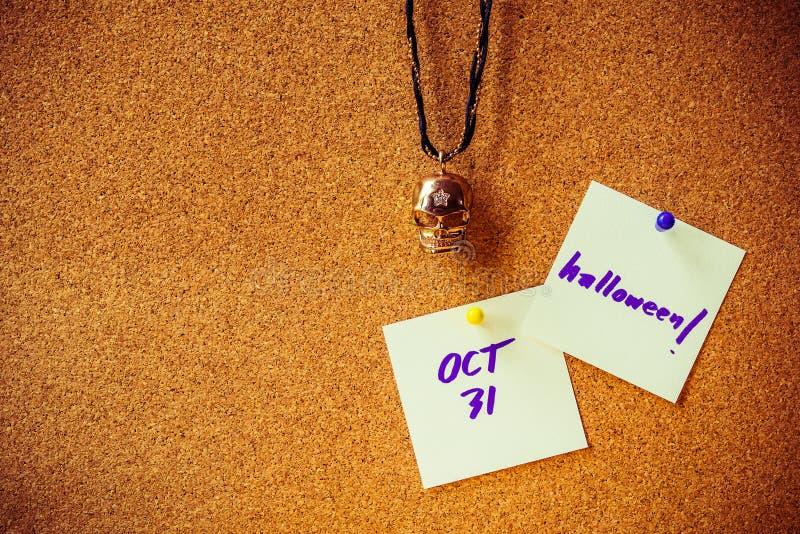 Purpurowy handwriting na białego papieru notatce, szpilce na korek desce z kolorem żółtym i purpury szpilce, metal czaszki breloc zdjęcie royalty free