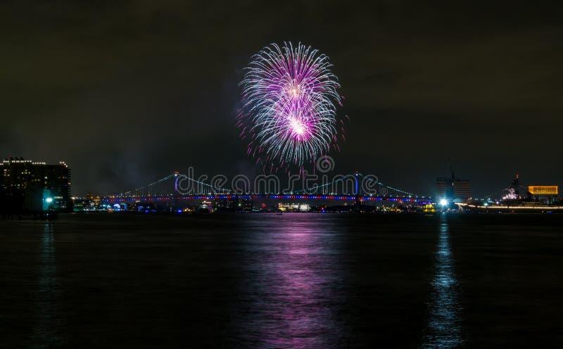 Purpurowy i Biały fajerwerku wybuch nad miasto mostem, Filadelfia zdjęcia stock