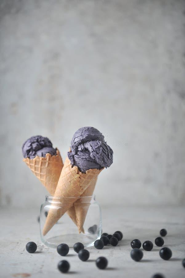 Purpurowy lody w szkle z czarną jagodą rozprzestrzenia na ziemi na concreat tle fotografia royalty free