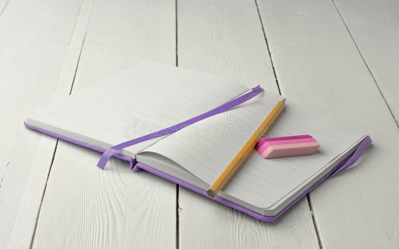 Purpurowy notatnik z ołówkiem i gumką na białym drewnianym backgr obraz stock
