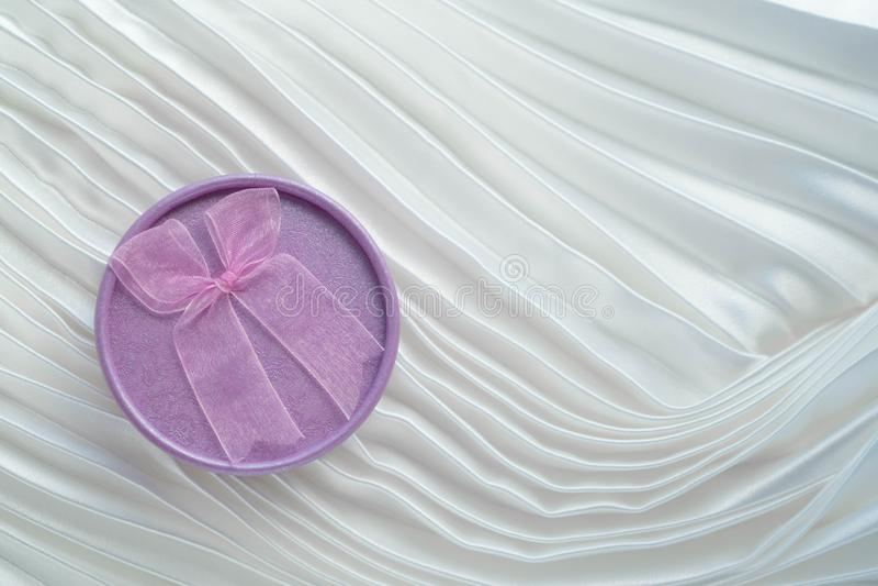 Purpurowy round kształta prezenta pudełko z menchiami ono kłania się na białym fałdowym atłasowym tle Dla projekta karty dla wale zdjęcie royalty free