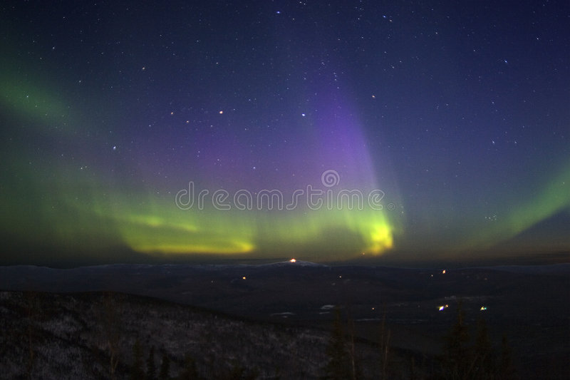 Purpurrot-grün-gelbliche Nordleuchten im sternenklaren Himmel über Hügel t lizenzfreie stockfotos