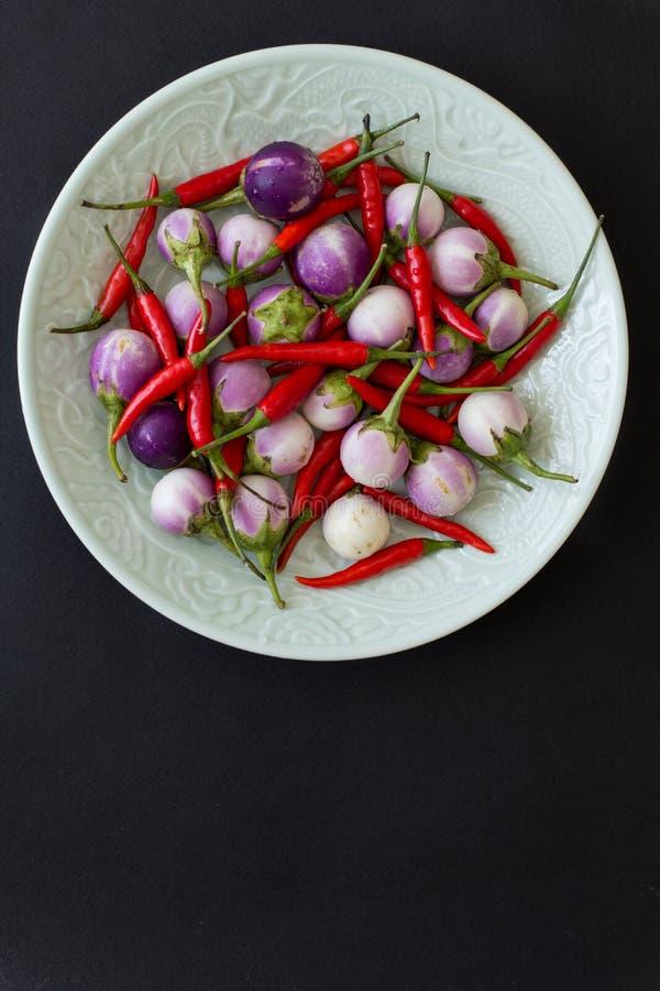 Purpurrote Auberginen und heißer roter Paprika auf einer grünen Platte auf einem schwarzen Hintergrund Kopieren Sie Platz stockfoto
